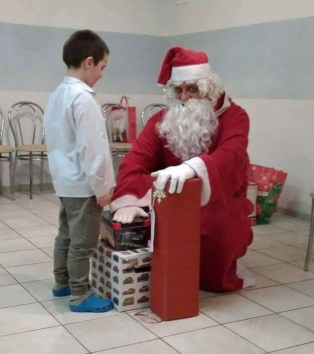 Zdjęcie, mikołaj wręcza chłopcu prezent