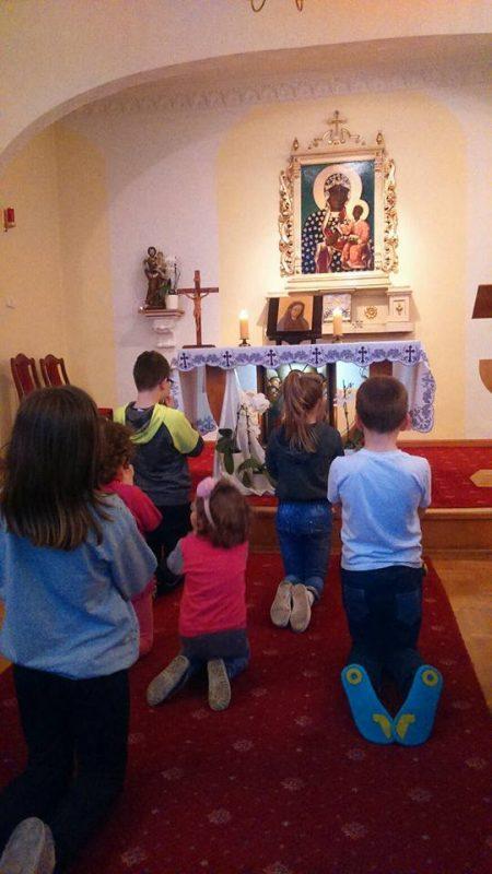grupka dzieci modli się do obrazu Matki cierpliwie słuchającej w kaplicy