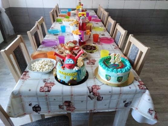 Stół urodzinowy na którym stoją słodycze talerzyki kubeczki i dwa torty