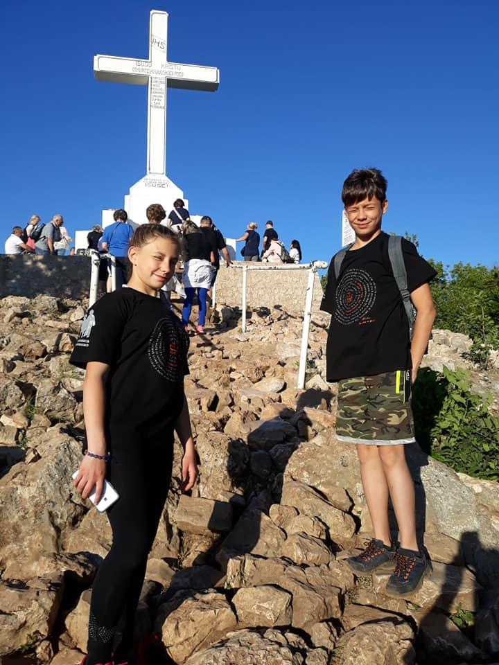 chłopiec i dziewczynka stoją na kamieniach w oddali widać krzyż