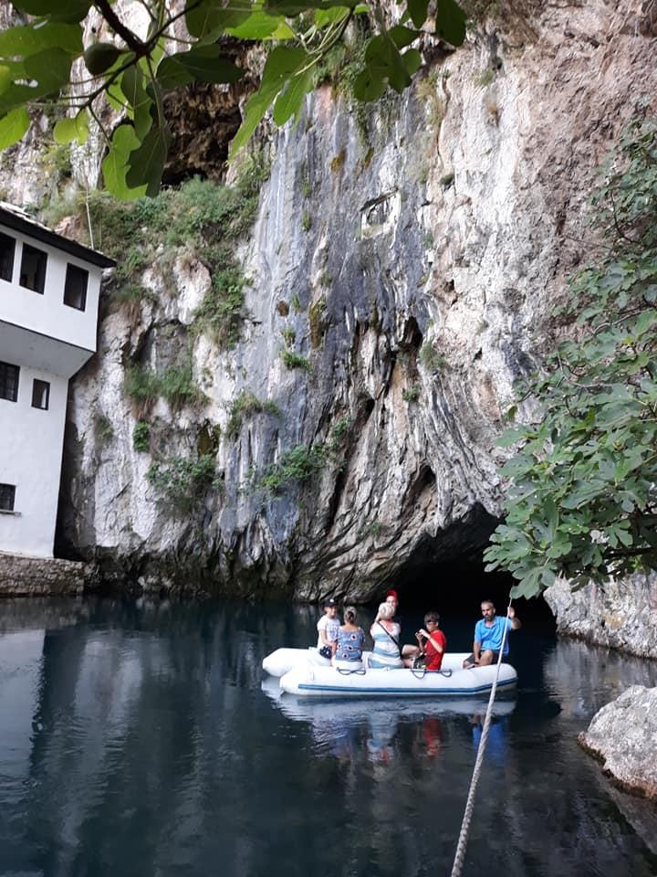 grupa ludzi płynie pontonem widać skały i jaskinie
