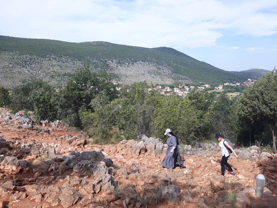 dziewczynka i Siostra Zakonna idą po kamieniach