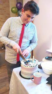 Zdjęcie przedstawia chłopca krojącego torta urodzinowego