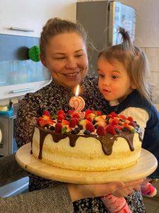 Zdjęcie przedstawia kobietę tzrymającą dziewczynkę na rękach, która dmucha świeczkę na torcie.