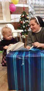 Zdjęcie przedstawia siostrę zakonną i mała dziewczynkę, które otwierają wielki prezent urodzinowy