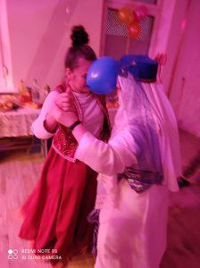 Dwie przebrane kobiety tańczą z balonem między głowami