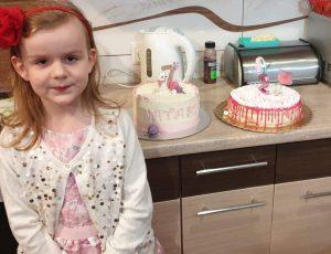 Zdjęcie pzredstawia dziewczynkę, która stoi obok szafki na której stoją dwa torty urodzinowe