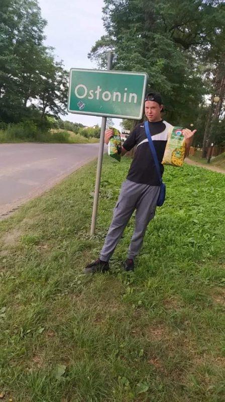 Chłopiec stoi przy znaku z nazwa miasta Osłonin